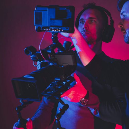 Two Caucasian Men Film Camera Crew Consulting Newly Taken Footage Reviewing on Large Digital Storage Display. Digital Videography Industry Theme.